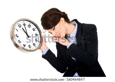 Tired business woman holding clock in hands. - stock photo