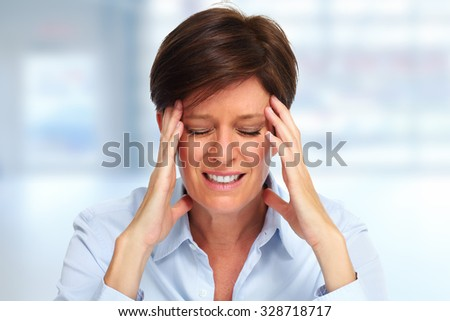 Tired business woman with headache migraine over blue background. - stock photo