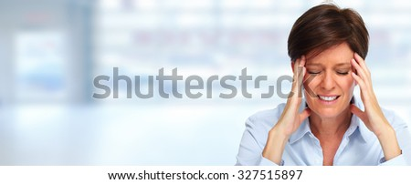 Tired business woman with headache migraine over blue banner. - stock photo