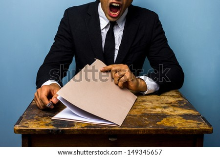 Tired businessman looking over documents - stock photo