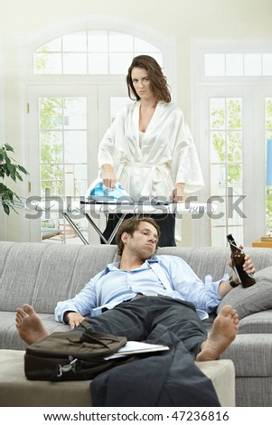 Tired businessman resting on couch with beer in hand. Angry wife ironing in the background. - stock photo