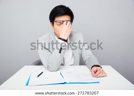 Tired businessman sitting at the table and rubs his nose in office - stock photo