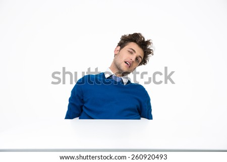 Tired businessman sitting at the table over white background - stock photo