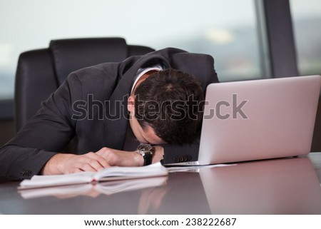 Tired businessman sleeping on a laptop - stock photo