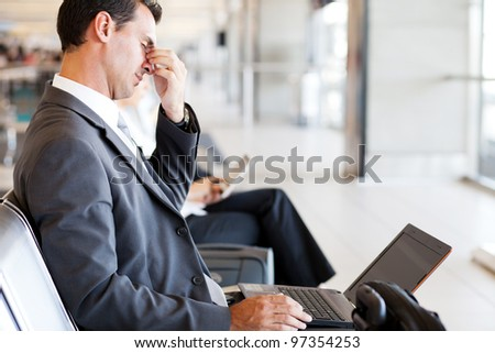 tired businessman taking a break at airport - stock photo