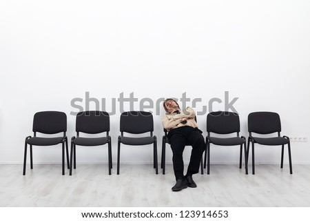 Tired businessman waiting - sitting on a chairs row - stock photo