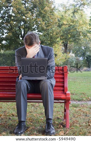 Tired businessman with laptop sitting on a park bench - stock photo