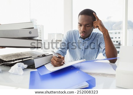 Tired businessman writing notes at desk in the office - stock photo