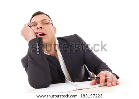 tired businessman yawning and sleeping at work with pen in hand - stock photo