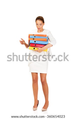 Tired businesswoman carrying heavy binders - stock photo