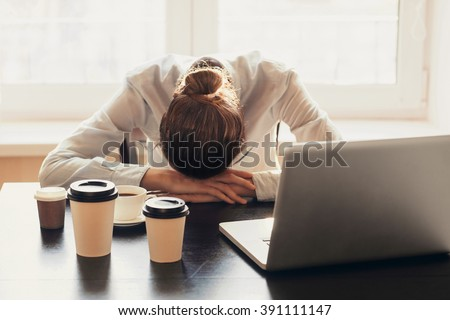 Tired businesswoman in the office - stock photo