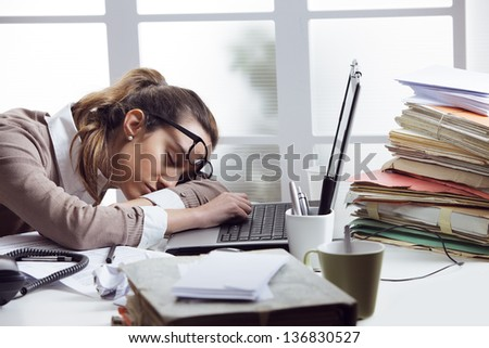 Tired businesswoman sleeping on the desk, in front of the computer screen. - stock photo