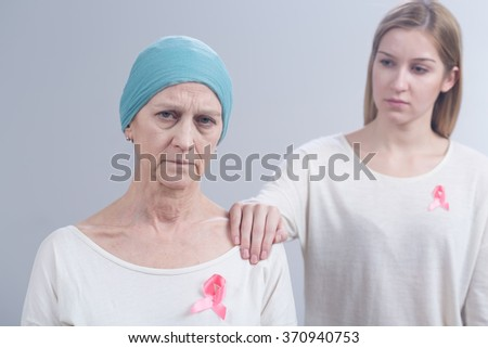 Tired cancer woman with headscarf and girl with pink ribbon holding hand on her arm - stock photo