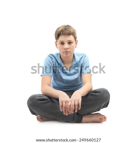 Tired caucasian 12 years old childen boy in a blue t-shirt sitting in a lotus position, full shot composition isolated over the white background - stock photo