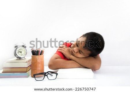 tired child lying and sleeping on the books - stock photo