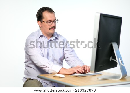 Tired employee in glasses asleep while working on computer - stock photo