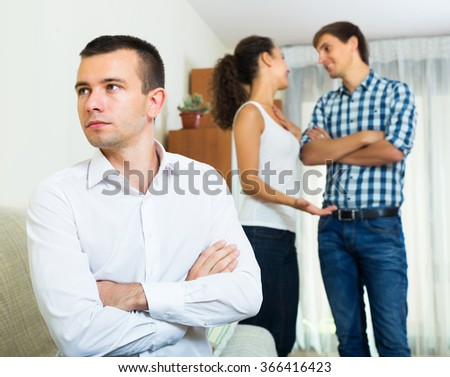 Tired ex-lover watching girlfriend leaving him for another man indoors - stock photo