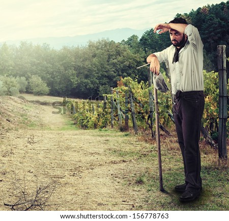Tired Farmer in the vineyard leaning on the hoe - stock photo