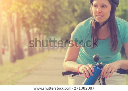 Tired female cyclist stopped to catch a breath. - stock photo