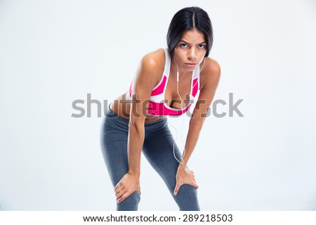 Tired fitness woman with headphones resting over gray background. Looking at camera - stock photo