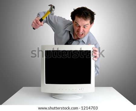 Tired, freaked-out business man preparing to smash a computer monitor with a hammer. - stock photo