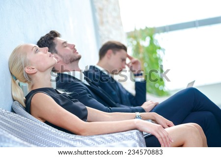 Tired from work. Tired businessman sitting in board room and bowed head back to rest. Businesspeople sitting in a line and dressed in formal wear. - stock photo