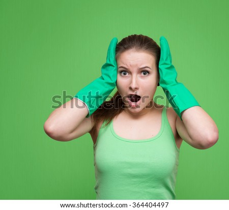 Tired frustrated and shocked cleaning woman screaming. Stressed spring cleaning woman in  green rubber gloves looking at camera. Isolated on green background - stock photo