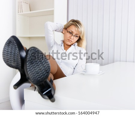 Tired girl in the office. Resting kicking on the table - stock photo