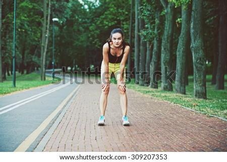 tired girl jogging at morning park - stock photo