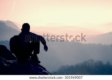 Tired hiker with sporty backpack sit on rocky peak and watching into deep misty valley bellow. Sunny spring daybreak - stock photo