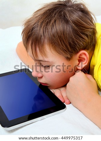 Tired Kid with Tablet Computer on the Bed - stock photo