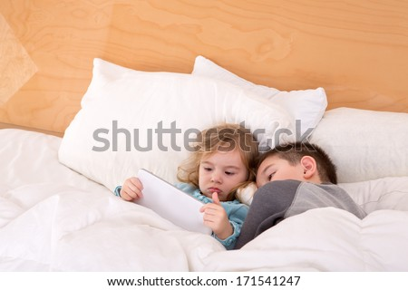Tired little brother and sister snuggling up together in a warm comfortable bed as they read a bedtime story on a tablet computer before falling asleep - stock photo