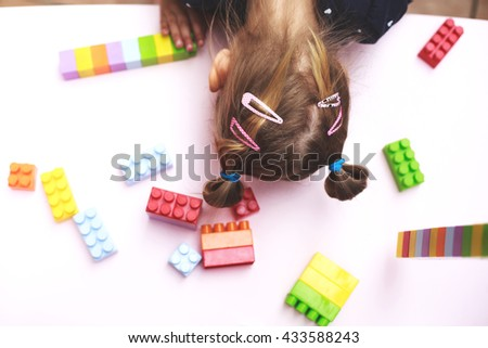 Tired little girl sitting at table next to her parts of constructor while playing. - stock photo