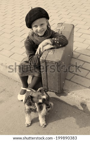 tired little girl sitting on the road with a dog and a suitcase - stock photo