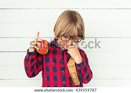 Tired little schoolboy holding book and red apple, wearing white red and blue plaid shirt and black frame eyeglasses, standing against white wooden background. Back to school concept - stock photo