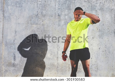 Tired male runner rubbing his forehead while resting after workout against cement wall background with copy space area for your text message or advertising, muscular athlete resting after fit training - stock photo