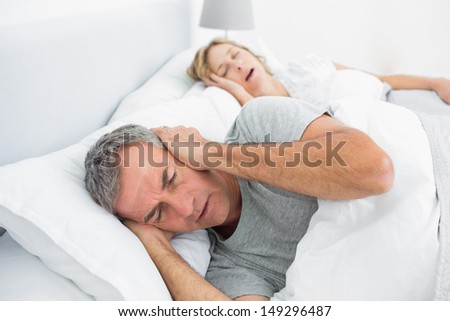 Tired man blocking his ears from noise of wife snoring in bedroom at home - stock photo