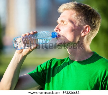 Tired man drinking water from a plastic bottle after fitness - stock photo