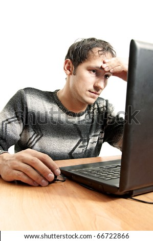 tired man sits at a table and sadly looks at the laptop screen having taken hand in head. Works at laptop computer at home - stock photo