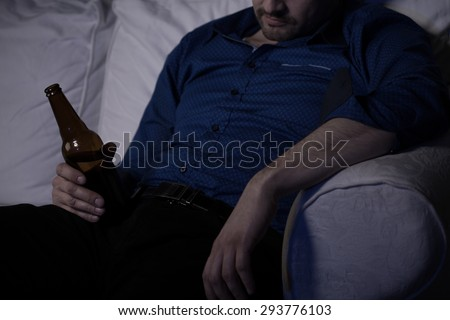 Tired man sleeping on couch with bottle of beer - stock photo