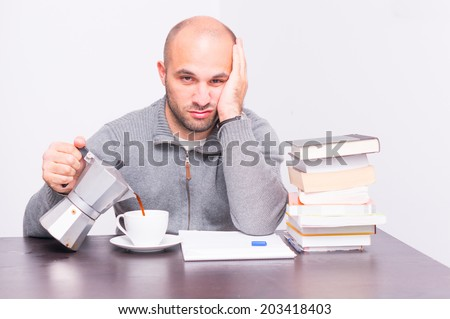 Tired man with books drinking coffee - stock photo