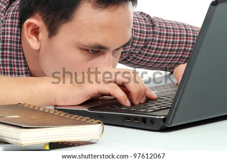 Tired man with head down on laptop - stock photo