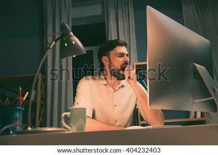 Tired man yawning after long working day - stock photo