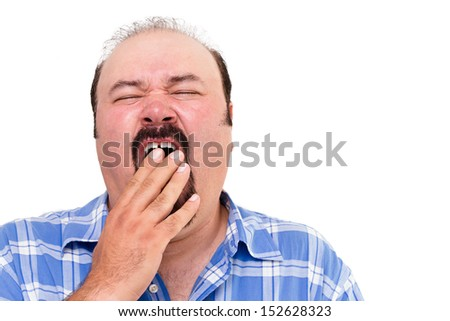 Tired man yawning with his hand to his mouth as he tries to fight off his exhaustion, isolated on white - stock photo
