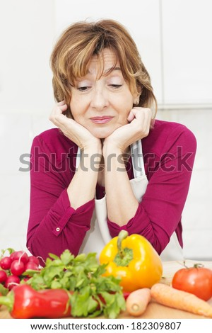 Tired mature woman of preparing meals. - stock photo