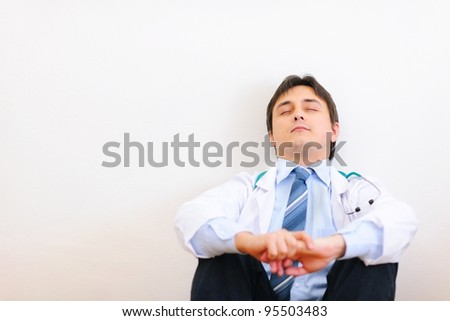 Tired medical doctor sitting on floor and relaxing - stock photo
