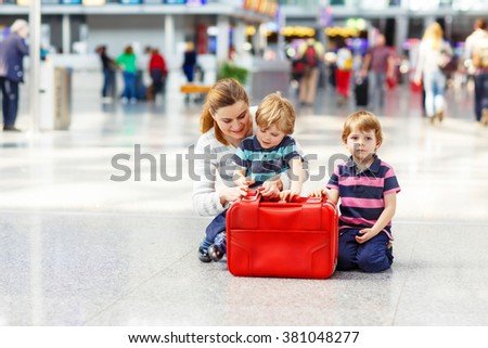 Tired mother and two little sibling kids boys at the airport, traveling together. Angry family waiting. Canceled flight due to pilot strike. - stock photo