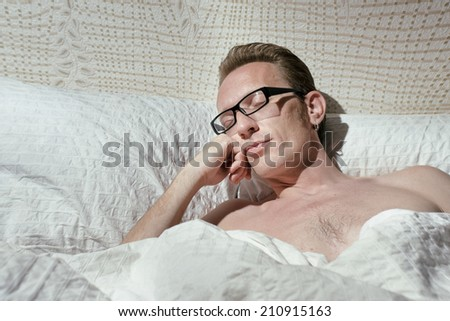 Tired naked handsome mid-ages man slept even not to pull off the eyeglasses.  - stock photo