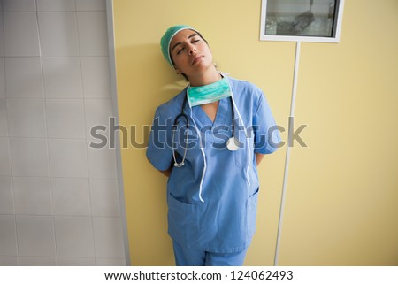 Tired nurse leans against wall with hands behind back in hospital room - stock photo
