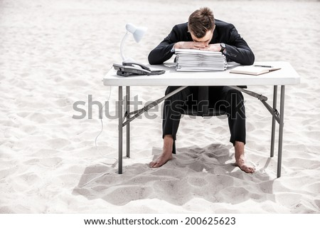 Tired of office work. Frustrated young businessman leaning his head at the table standing on sand - stock photo